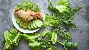 Un pezzo di carne succoso su un piatto bianco ha ornato con le foglie verdi della lattuga Composizione commovente sulla tavola stock footage
