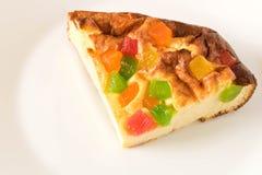 Un pezzo di casseruola della ricotta con i frutti canditi su un piatto bianco Fine in su fotografia stock