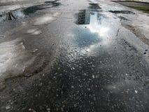 Un pezzo di cielo della molla, che è riflesso nella pozza fusa sulla strada asfaltata fotografie stock