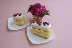 Un pezzo di dolce con i mirtilli ed i lamponi è sulla tavola con un colore rosa Fotografie Stock