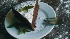 Un pezzo di dolce del brownie del cioccolato su un piatto bianco ha decorato con le foglie di menta fresca accanto alla forcella archivi video