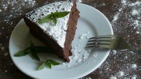Un pezzo di dolce del brownie del cioccolato su un piatto bianco ha decorato con le foglie di menta fresca accanto alla forcella video d archivio