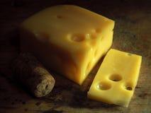 Un pezzo di formaggio su un bordo di legno Immagini Stock Libere da Diritti