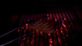 Un pezzo di pane è cotto sulla griglia nel forno con i carboni di fuoco senza fiamma sul fondo Le mani del cuoco unico girano il  stock footage