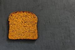 Un pezzo di pane di segale nero su un fondo nero Fotografie Stock