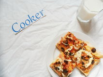 un pezzo di pizza casalinga su un piatto, un bicchiere di latte su un fondo bianco Immagini Stock