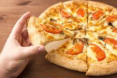 Un pezzo di pizza deliziosa in sua mano Pizza del fungo con formaggio ed i pomodori Immagine Stock