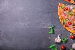 Un pezzo di pizza saporita con le verdure, la carne e le salse su un fondo di pietra grigio scuro Un posto per l'iscrizione immagini stock