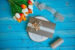 Un pezzo di pizzo del cotone con i fiori di carta e pezzo di carta marrone su un taglio dell'albero Fotografia Stock