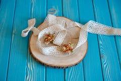 Un pezzo di pizzo del cotone con i fiori di carta su un taglio dell'albero Immagine Stock