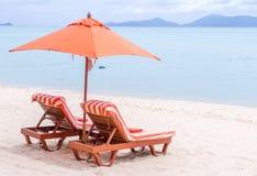 Un pezzo di terra coltivato a e un ombrello due arance sulla spiaggia Immagine Stock Libera da Diritti