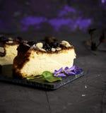 Un pezzo di torta di formaggio su un fondo nero spruzzato con almon Fotografia Stock
