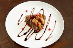 Un pezzo di torta di mele con il papavero sul piatto bianco decorato con i semi del melograno e la crema freschi del cioccolato G Fotografia Stock Libera da Diritti