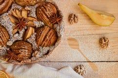 Un pezzo di torta in polvere della pera decorata con il panno e cucchiaio bianco, arance secche, noci, stelle dell'anice e pera f Immagine Stock