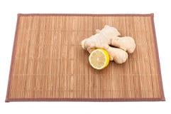 Un pezzo di zenzero e una frazione del limone fresco su una stuoia di bambù immagine stock