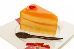 Un pezzo solo del dolce arancio con il piccolo cucchiaio di legno fotografia stock