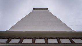 Un phare moderne se tenant contre un angle faible de ciel nuageux Photo stock