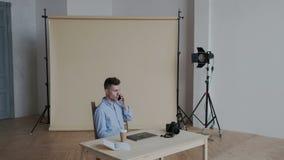 Un photographe élégant et occupé vient à son lieu de travail dans un studio moderne de photo Il parle au téléphone, met la caméra clips vidéos