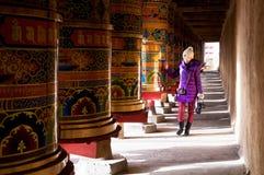 Un photographe féminin marchant par la roue de prière Photos stock