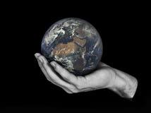 Un pianeta Terra della tenuta della mano isolato sul nero Immagine Stock