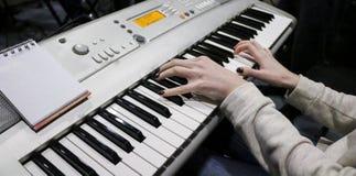 Un pianista de la chica joven juega el piano electrónico con su música preferida Las manos agraciadas femeninas tocan las llaves  imagen de archivo