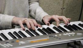 Un pianista de la chica joven juega el piano electrónico con su música preferida Las manos agraciadas femeninas tocan las llaves  foto de archivo libre de regalías