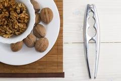Un piatto bianco del nocciolo della noce e un intero dado su bianco di legno t Fotografia Stock Libera da Diritti