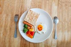 Un piatto bianco della prima colazione del bambino decorato con l'omelette sorridente delle pecore, il pane arrostito, la salsicc fotografia stock