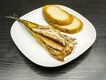 Un piatto bianco dello sgombro affumicato con le fette di pane ha preparato per mangiare immagini stock libere da diritti