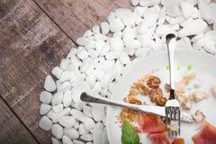 Un piatto con il resti di alimento ed il vetro invertito su un bianco lapida il fondo cutlery Copi lo spazio Fotografia Stock