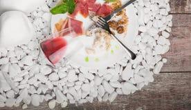 Un piatto con il resti di alimento ed il vetro invertito su un bianco lapida il fondo cutlery Copi lo spazio Immagini Stock