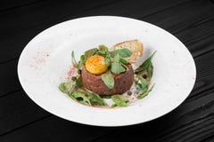 Un piatto con il tartaro e il rucola della bistecca Fotografia Stock