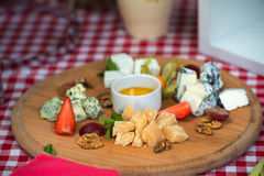 Un piatto con quattro generi di formaggio, di uva, di noci e di miele Vista superiore Fotografie Stock Libere da Diritti