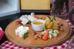 Un piatto con quattro generi di formaggio, di uva, di noci e di miele Vista superiore Fotografia Stock