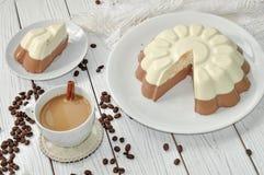 Un piatto con un dolce appetitoso di strato della mousse (vaniglia e cioccolato) e una tazza del caffè del latte su una superfici immagine stock