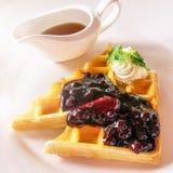 Un piatto decadente della prima colazione delle cialde belghe, della panna montata e dello sciroppo d'acero fotografie stock libere da diritti