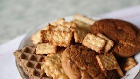 Un piatto dei biscotti, la mano prende uno stock footage