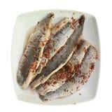 Un piatto del filetto di pesce salato in olio e dei condimenti su un piatto Alimento su un fondo isolato bianco Menu e cena del r fotografia stock