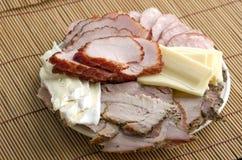 Un piatto del prosciutto affettato, della salsiccia affumicata, dell'arrosto di maiale e del formaggio sopra Fotografie Stock
