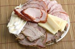 Un piatto del prosciutto affettato, della salsiccia affumicata, dell'arrosto di maiale e del formaggio sopra Immagine Stock