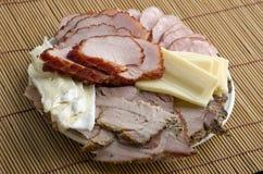 Un piatto del prosciutto affettato, della salsiccia affumicata, dell'arrosto di maiale e del formaggio sopra Fotografia Stock Libera da Diritti