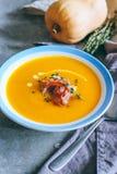 Un piatto della minestra della zucca con un jamon, un aglio, un timo e una crema Immagini Stock