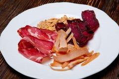 Un piatto di birra con la spigola del manzo ed i peperoncini rossi dell'arachide Fotografia Stock