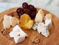 Un piatto di legno con l'uva del parmigiano con le noci ed il miele immagini stock libere da diritti