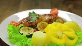 Un piatto girante con un piatto di pollo arrostito e un piatto laterale delle verdure stock footage