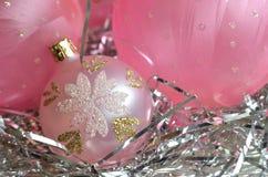 Un piatto madreperlaceo con gli ornamenti rosa glassati della palla di Natale sulla decorazione d'argento dei capelli con lo spaz Immagine Stock Libera da Diritti