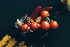 Un piatto nero della ciliegia fresca deliziosa dei pomodori che si trova su un tagliere di legno Le erbe sono usate come decorazi fotografia stock libera da diritti