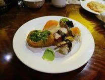 Un piatto in pieno dei sushi con un'ombra di wasabi fotografie stock