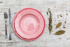 Un piatto rosa sulla tavola con gli apparecchi per mangiare Immagine Stock