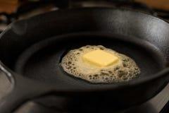 Un picchiettio di burro che si fonde su una padella nera del ghisa immagini stock